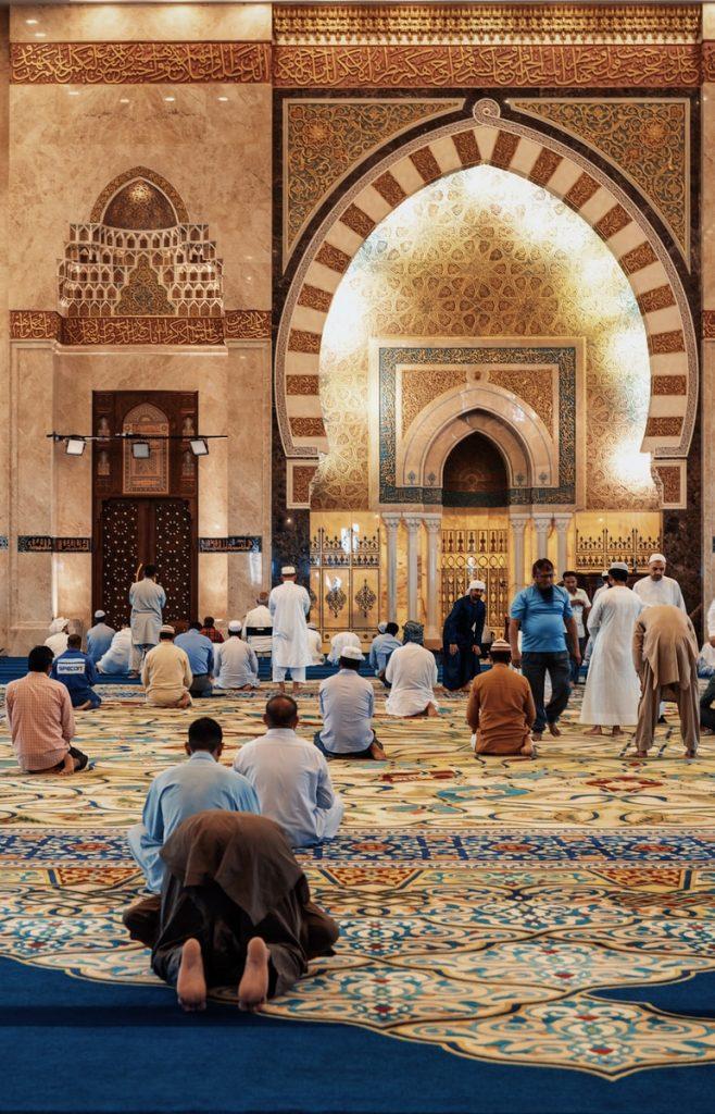men kneeling and bowing inside building