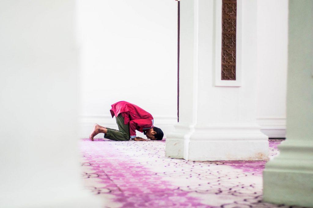 man praying in a bowed posture